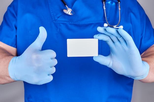 青いラテックス手袋を身に着けている男性医師は、白紙の名刺を持っています。