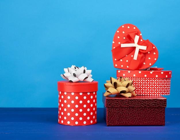 Красные картонные коробки с подарками на синем фоне