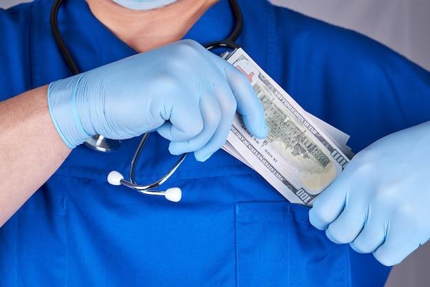 男性医師は彼のシャツのポケット、賄賂を取ることの概念にたくさんのドルを置きます