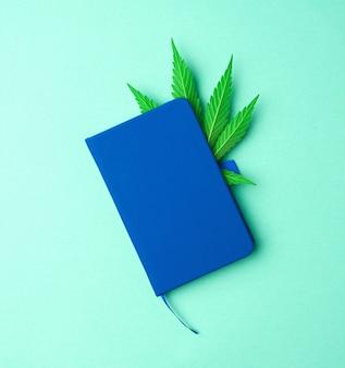 Синий блокнот и зеленый лист конопли на светло-зеленом фоне