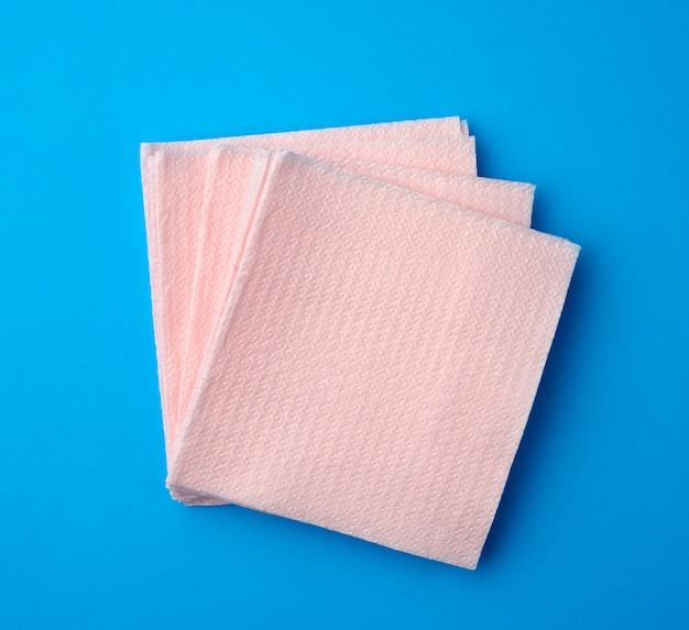 Розовые бумажные одноразовые салфетки на синем фоне