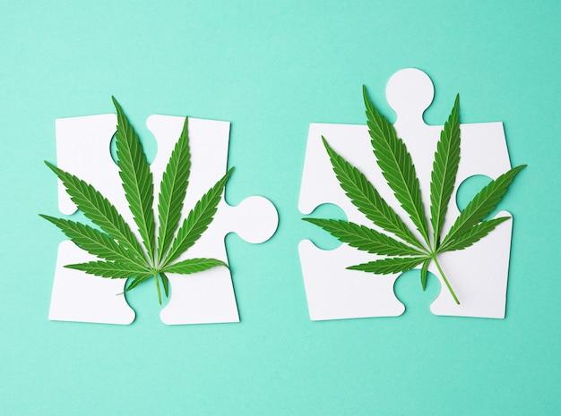 Зеленые листья конопли и большие белые бумажные пазлы на зеленом фоне
