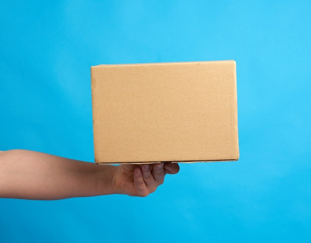 手は青色の背景に紙の茶色の段ボール箱を保持します