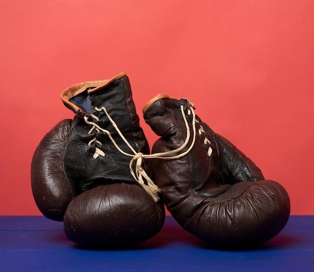 赤の背景に茶色の革ヴィンテージボクシンググローブ