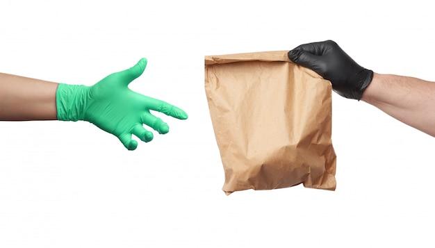 黒いラテックス手袋をはめた手は完全な茶色のパッケージを保持し、緑色の手袋をはめた女性の手は物体に手を伸ばします