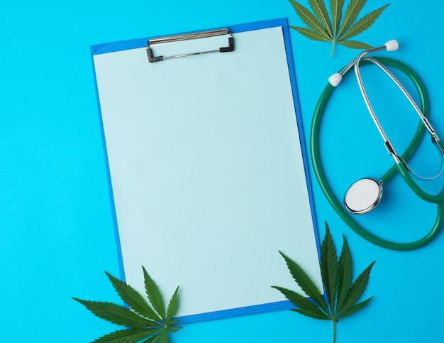 Медицинский стетоскоп и зеленый лист конопли на синем фоне