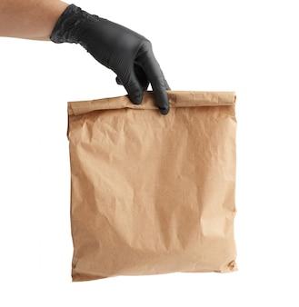 黒のラテックス手袋の手は茶色のクラフトペーパー、リモートおよび非接触の食品配達、注文の安全な受け取り、白い背景の概念の完全な紙袋を保持しています。