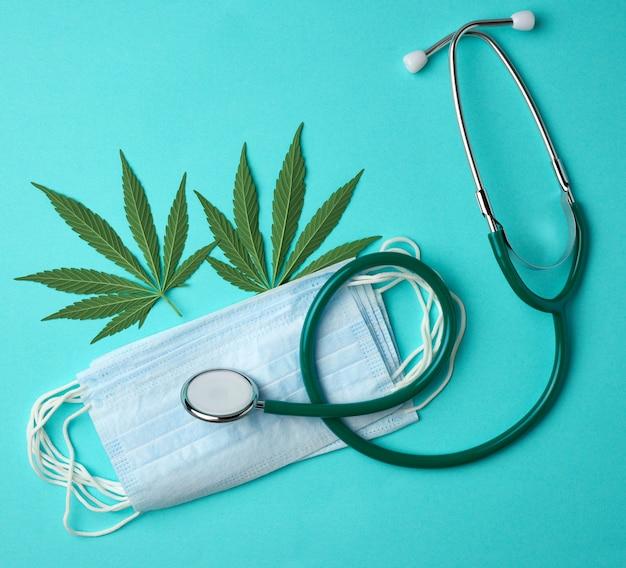 Медицинский стетоскоп, одноразовая маска, латексные стерильные перчатки и лист зеленой конопли