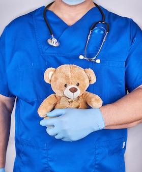 茶色のテディベアを保持している青い制服と古いラテックス手袋の医者