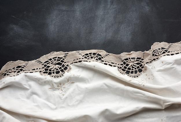 Белое кухонное текстильное кружевное полотенце сложенное на черном деревянном столе, вид сверху