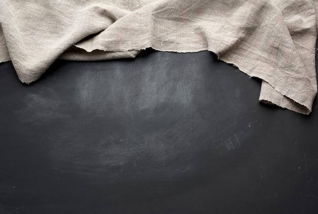 Серое кухонное текстильное полотенце сложенное на черном деревянном столе, вид сверху
