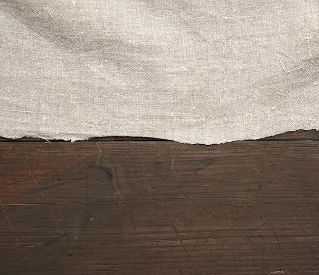 Серое кухонное текстильное полотенце сложенное на коричневом деревянном столе из старых досок