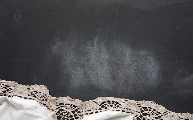 Белое кухонное текстильное кружевное полотенце сложенное на черном деревянном столе