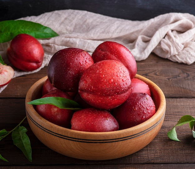 テーブルの上の木製のボウルに熟した赤い桃