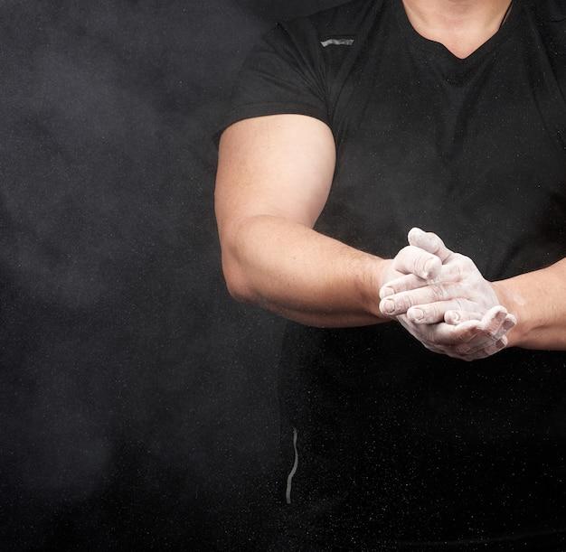 黒い制服を着た筋肉の運動選手が白いドライスポーツマグネシアで手をこすります