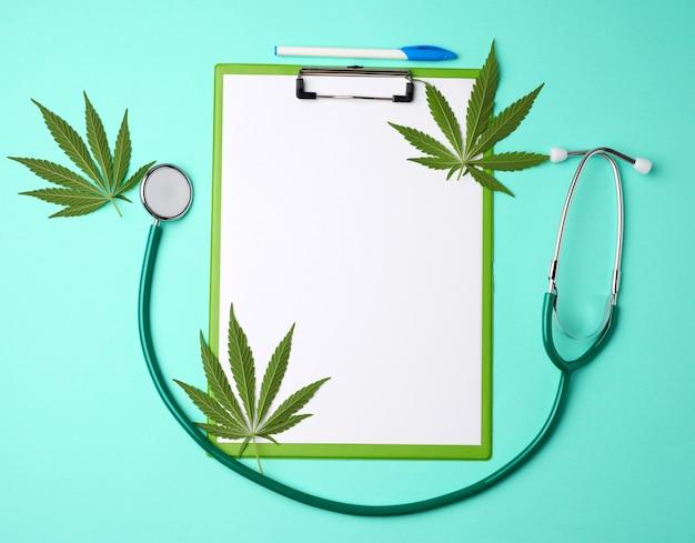 Медицинский стетоскоп и зеленые листья конопли на зеленом фоне