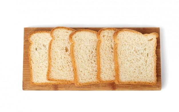 Свежий хлеб из белой пшеничной муки нарезать ломтиками на деревянной доске