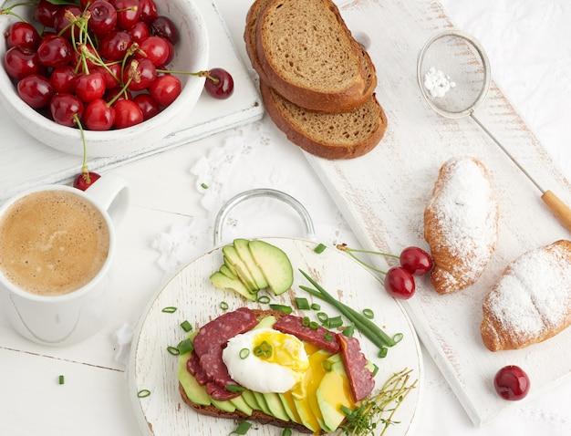 ポーチドエッグとアボカドのトースト、ラウンドボード、クロワッサンと熟した赤いチェリーの横、朝の朝食