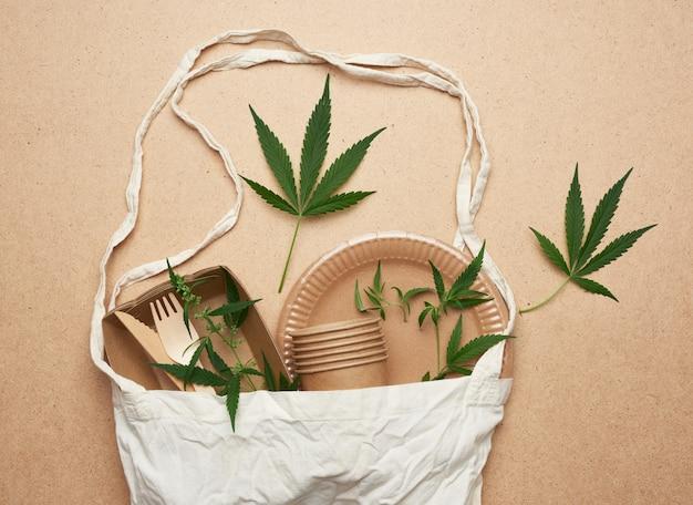 茶色のクラフトペーパー、緑の麻の葉から作られたテキスタイルバッグと使い捨て食器