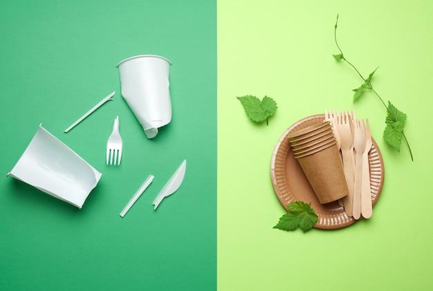 緑の背景に使い捨て食器からの非分解性プラスチック廃棄物と環境リサイクル材料からの皿のセット