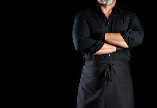 黒の制服を着た男性シェフが黒の背景、レストランやカフェのバナー、碑文の空きスペースに胸の前で腕を組んだ