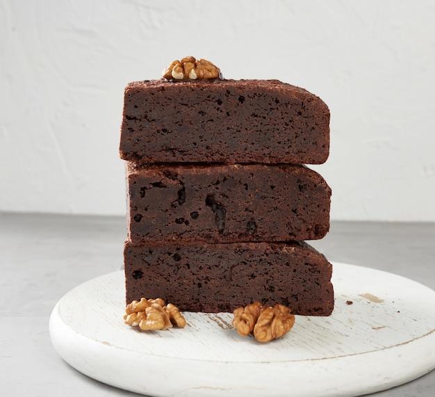 Стек испеченных кусочков пирожного шоколадный торт с орехами на деревянной доске, вкусный десерт
