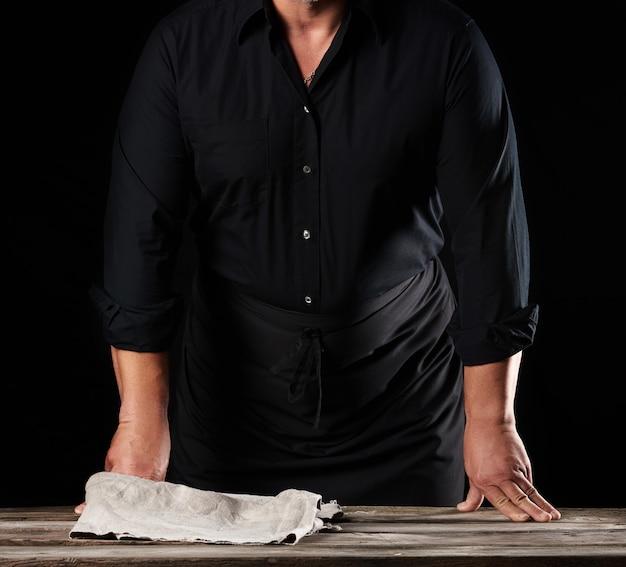黒いシャツとエプロンの男シェフが木製のテーブルのそばに立つ