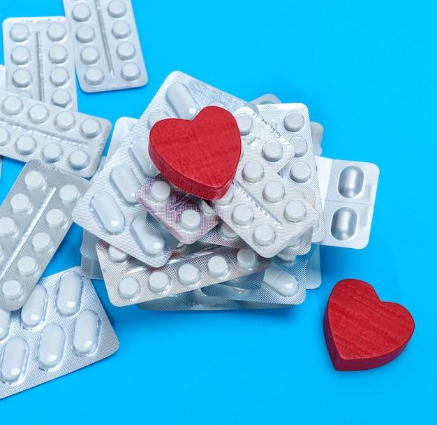 Стопка разных таблеток в упаковке и два красных сердечка