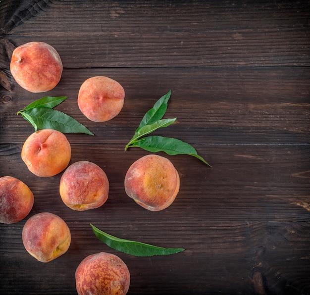 Спелые персики и зеленые листья