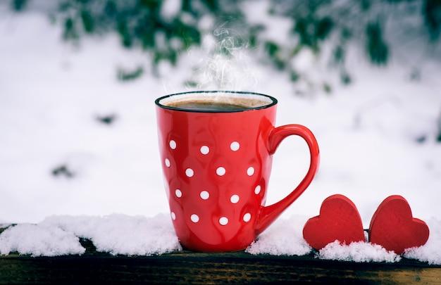 Красная кружка в горошек с горячим черным кофе