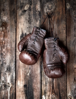 Очень старые кожаные коричневые боксерские перчатки висят на старой потертой деревянной стене