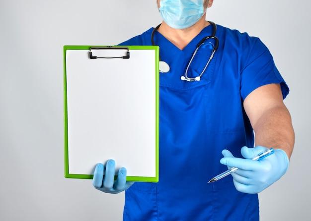 青い制服と滅菌ラテックス手袋の医者はペーパークリップを保持します