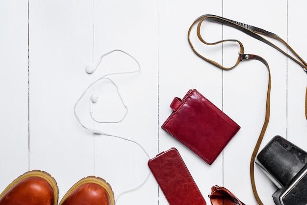 茶色の革製の財布、古いカメラ、ケースに入った携帯電話、ヘッドフォン