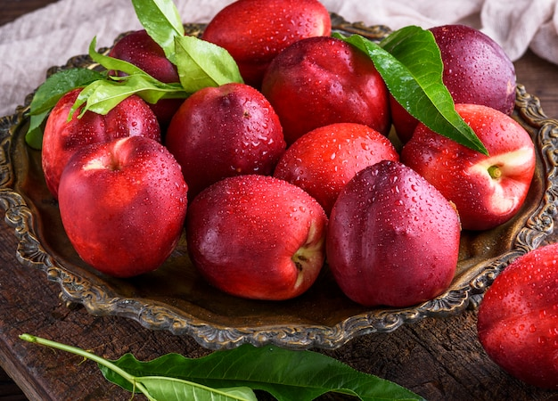 Красные спелые персики нектарин в железной тарелке