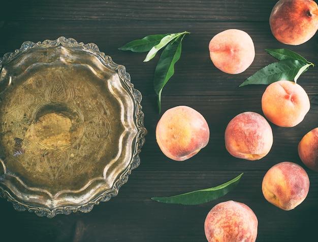 Спелые персики на деревянном коричневом фоне