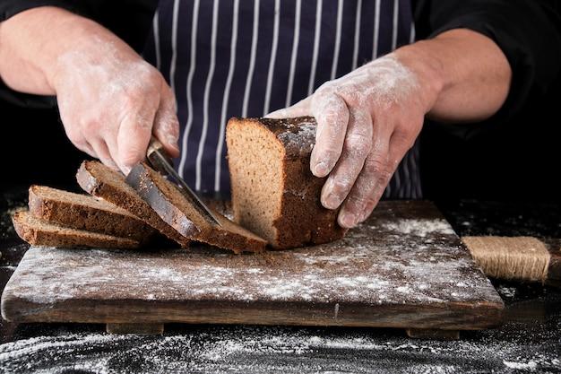 黒い制服を着たシェフが彼の手に包丁を持ってパンを切る