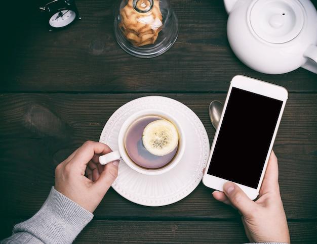 右の女性の手に黒い空白の画面を持つ白いスマートフォン