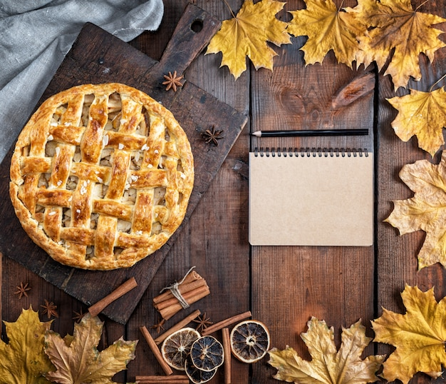 茶色の木の板、パイ生地に焼きたての丸いアップルパイ