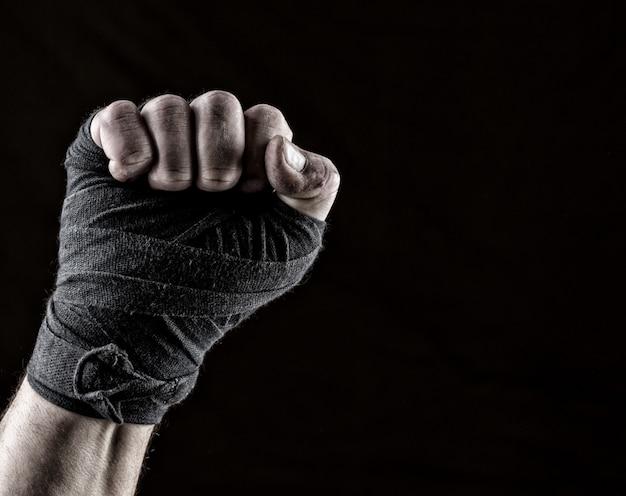 黒い繊維の包帯で包まれた運動選手の持ち上がった拳