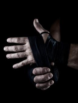 男はスポーツのための黒い織物包帯で彼の手を包みます