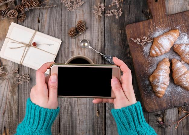 空白の黒い画面を持つスマートフォンを保持している緑のニットセーターで女性の手