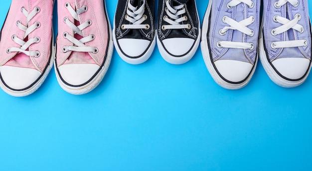 Три пары изношенной текстильной обуви на синем фоне