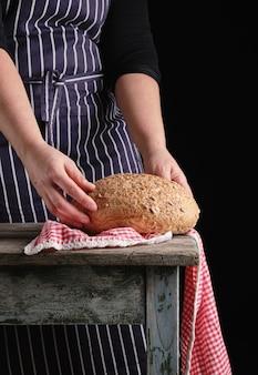 青のストライプのエプロンの女性は彼女の手で保持していますラウンドライ麦パン