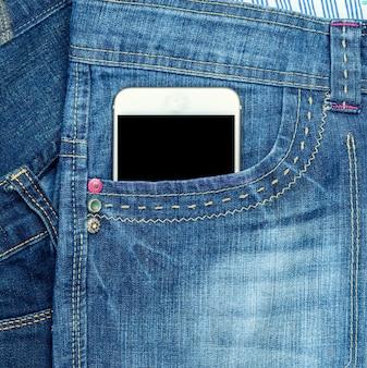 Смартфон с пустым черным экраном находится в переднем кармане синих джинсов