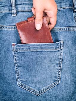 Коричневый кожаный кошелек лежит в заднем кармане синих джинсов