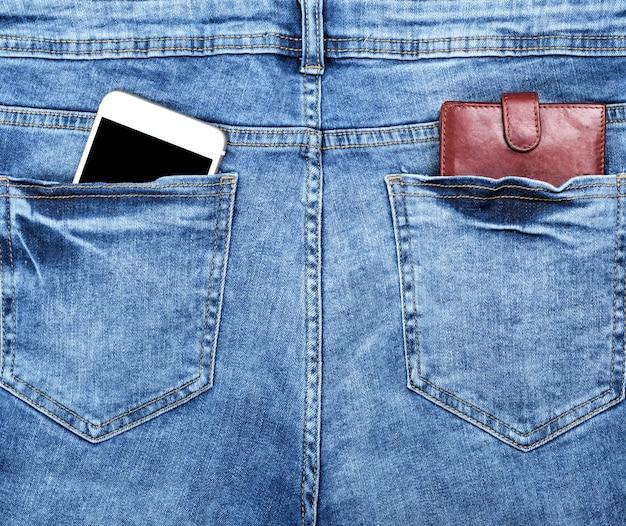 Коричневый кожаный кошелек и белый смартфон с пустым черным экраном в заднем кармане