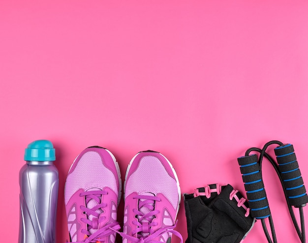 Розовые женские кроссовки, бутылка воды, перчатки и скакалка для спорта