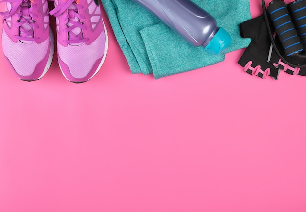 ピンクの女性用スニーカー、ボトル入り飲料水、手袋、スポーツ用縄跳び