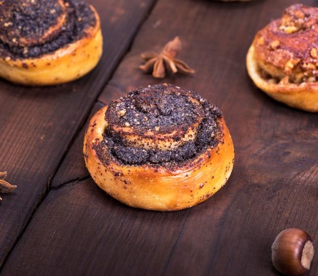 茶色の木製のテーブルの上の丸いケシとナットパン