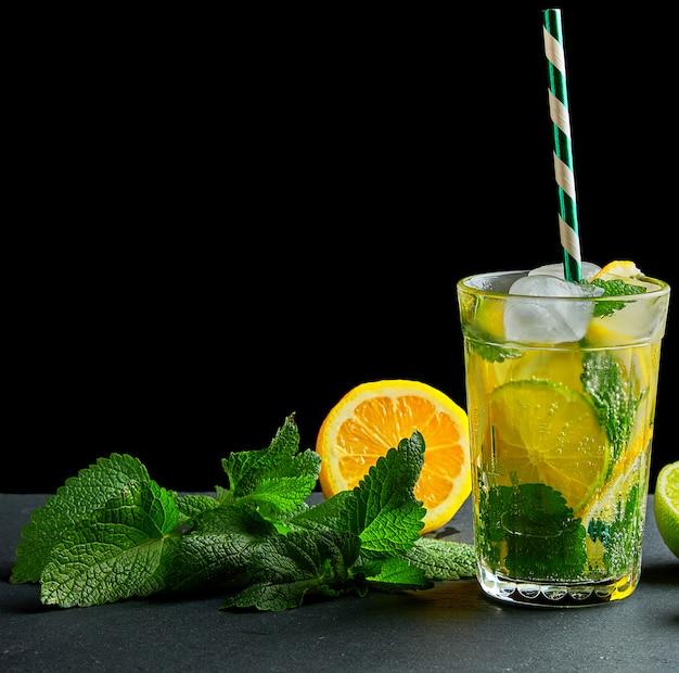 ガラスのレモン、ミントの葉、アイスキューブ、ライムのさわやかなドリンクレモネード